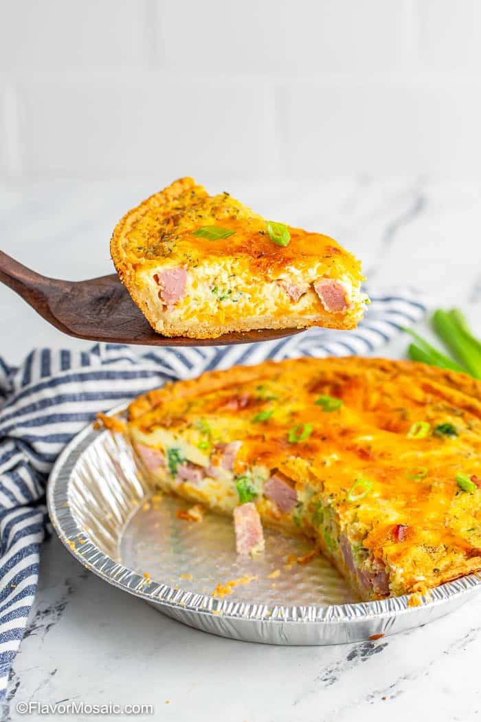 Spatula holding up 1 slice of Ham Broccoli and Cheese Quiche over the entire pie below with a blue and white napkin in the back.