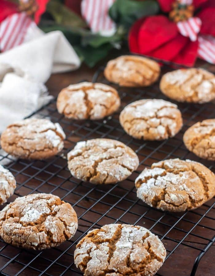 A Dozen Molasses Crinkle Cookies on a baking rack over a dark wood background with red and white bows and greenery in the background.