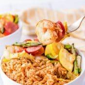 Cajun Shrimp And Sausage Sheet Pan Dinner served with Cajun Rice in a bowl.