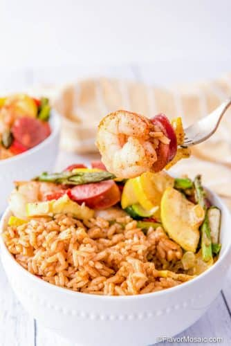 Cajun Shrimp And Sausage Sheet Pan Dinner served with Cajun Rice in a bowl.