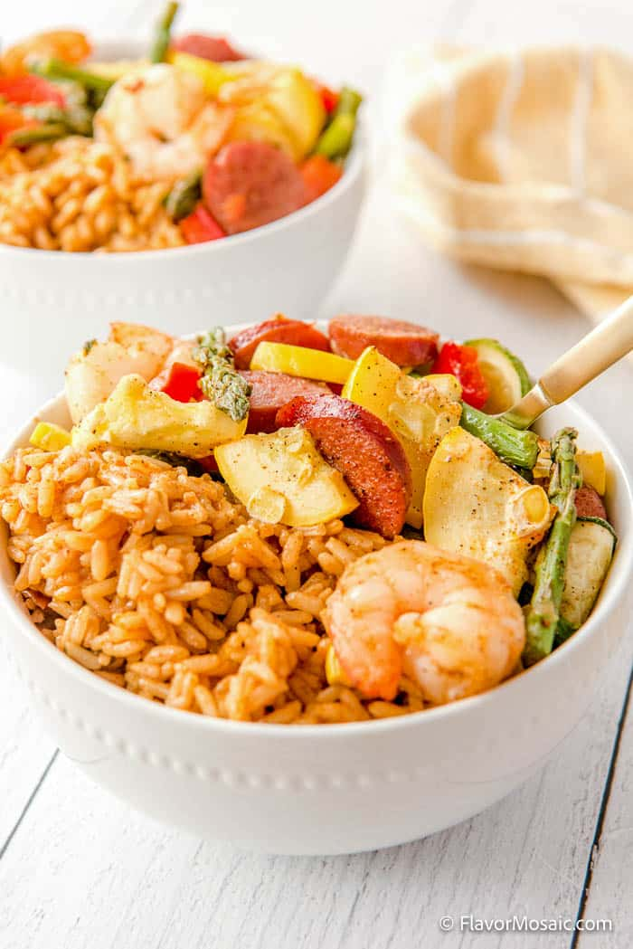 View of bowl with Cajun Shrimp and Sausage with dirty rice with another white serving bowl with more Cajun Shrimp and Sausage with a napkin in the top right in the background.
