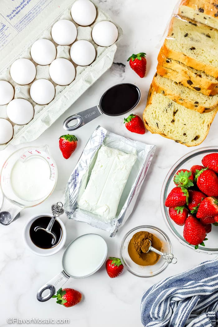 Overhead view of ingredients for Chocolate Strawberry French Toast Casserole including Eggs, Bread, Cream Cheese and fresh strawberries.