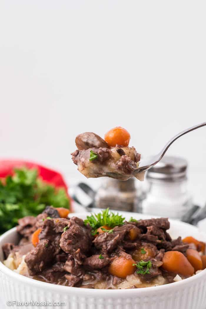 A spoonful of Instant Pot Beef Burgundy held over a white bowl of beef burgundy.