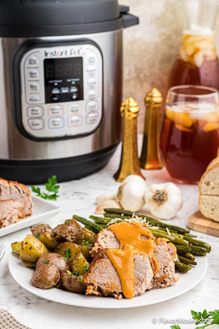Straight on view of slices of pork tenderloin on white dinner plate covered in an orange maple sauce served with new potatoes and green beans with 2 garlic cloves, salt and pepper shakers, instant pot, and glass of ice tea.