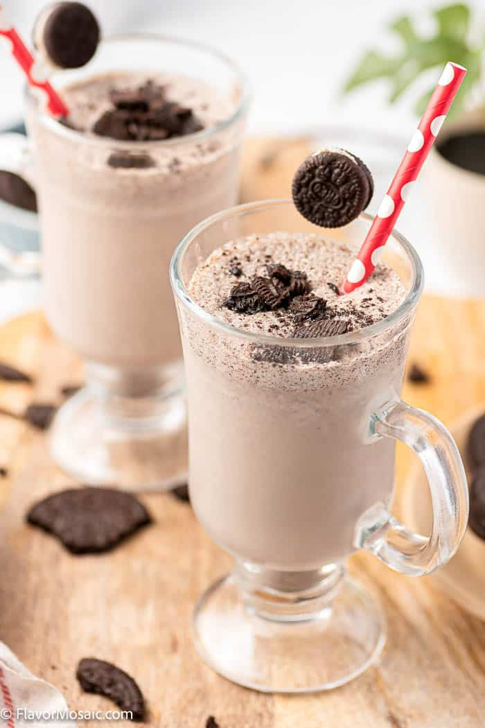 Two Tall Glasses with Oreo Milkshakes topped with Oreo pieces and surrounded by Oreo cookie pieces on a cutting board