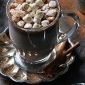 glass of Easy Nutella Hot Chocolate with mini marshmallows and dark background.