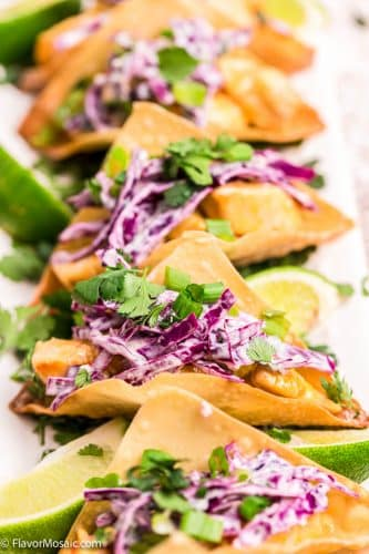 Several Chicken Wonton Tacos lined up vertically served with red cabbage slaw, cilantro and limes.