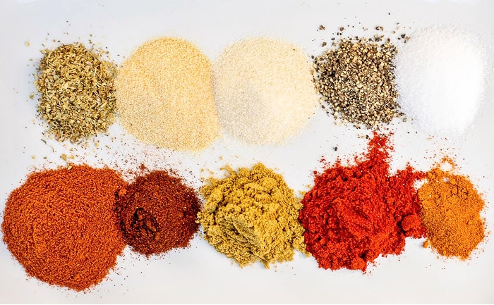 Overhead view of individual spices for Fajita Seasoning on a white background