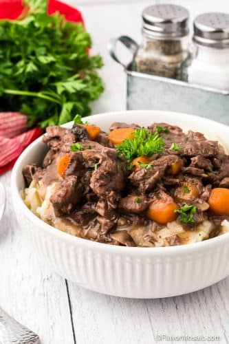 White bowl of Instant Pot Beef Burgundy with carrots and parsley over mashed potatoes.