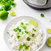 White Bowl of Cilantro Lime Rice with lime slice and surrounded by limes and cilantro in front of an Instant Pot.
