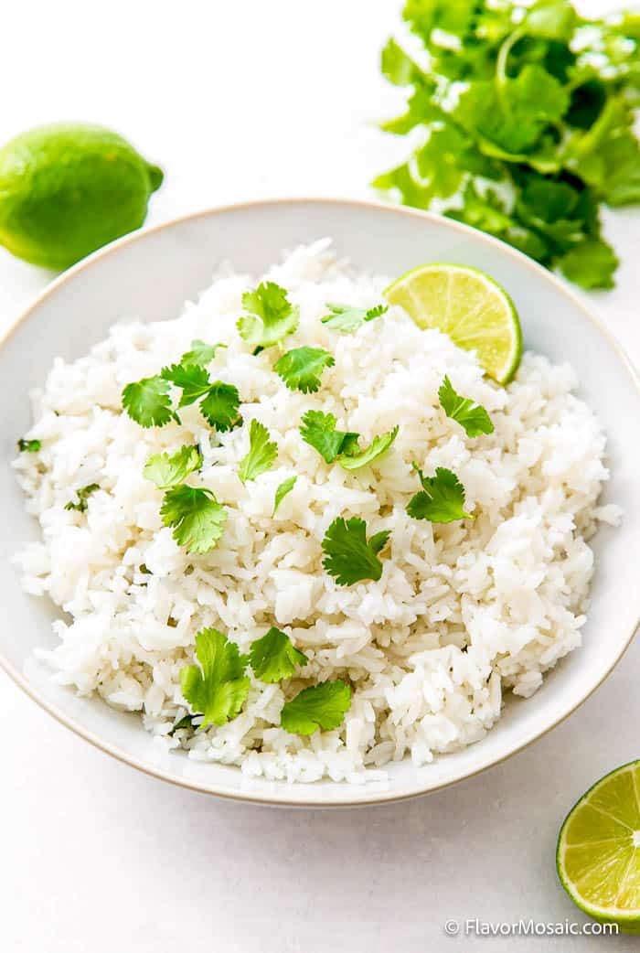 White bowl on white countertop with Cilantro Lime Rice with chopped cilantro and a slice of lime surrounded by limes and a bunch of cilantro.