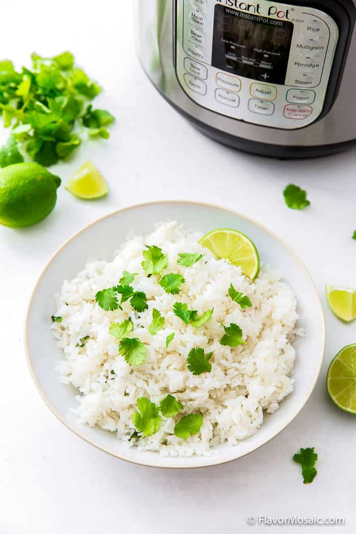 white bowl of cilantro lime rice surrounded by limes and cilantro on white countertop with a partial view of the front of an Instant Pot in the background.