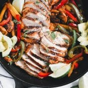 Overhead view of sliced skillet chicken fajitas in a cast iron skillet with sliced bell peppers, avocados, limes, and onions.