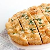 Golden Asiago Foccacia sitting on elevated white patter cut into slices.