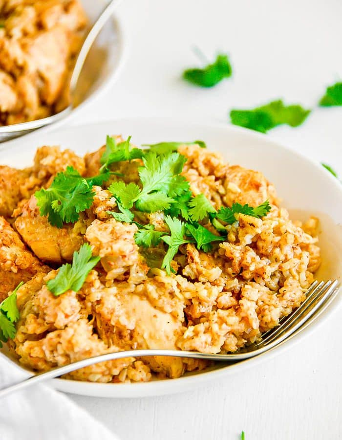 View of large white bowl of Instant Pot Chicken And Rice topped with chopped cilantro and surrounded by pieces of cilantro on white background with a partial view of another bowl of chicken and rice.