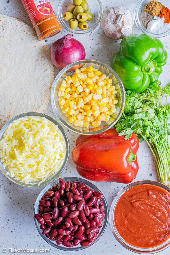 Overhead view of ingredients for vegetarian casserole with beans, corn red bell pepper, shredded cheese, onion, cilantro enchilada sauce and more.