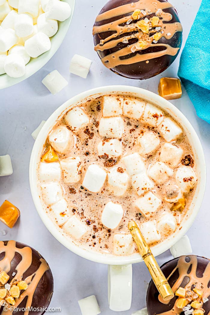 Overhead view of white cup of hot chocolate with mini marshmallows surrounded by 3 salted caramel chocolate bombs, mini marshmallows, caramel pieces, and a little of a blue napkin in the top right corder, and a bowl of mini marshmallows in the top left corner.