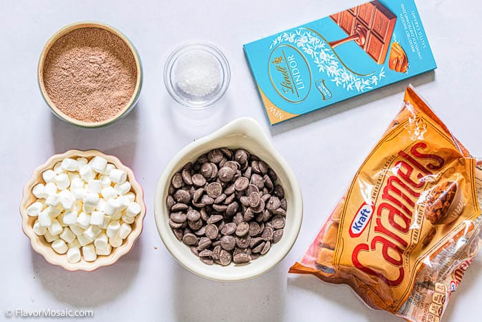 Overhead view of ingredients for Hot Chocolate Bombs - cocoa, mini marshmallows, chocolate chips, Lindt chocolate, caramel pieces
