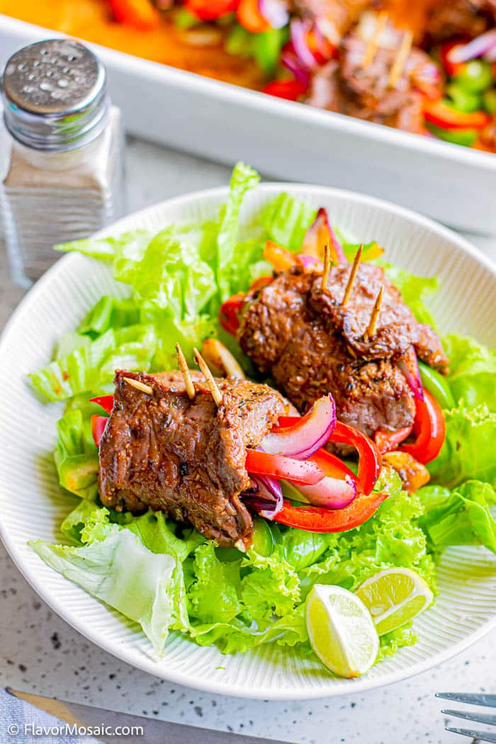 2 Steak Roll Fajitas wrapped around strips of red and green bell pepper and red onion sitting on top of green lettuce on top of a white dinner plate.