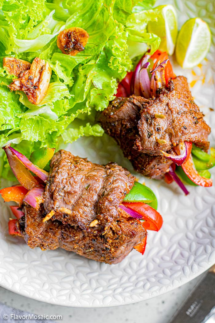 Overhead view of Steak Roll Fajitas with red and green peppers stick out sitting on white plate next to green salad.