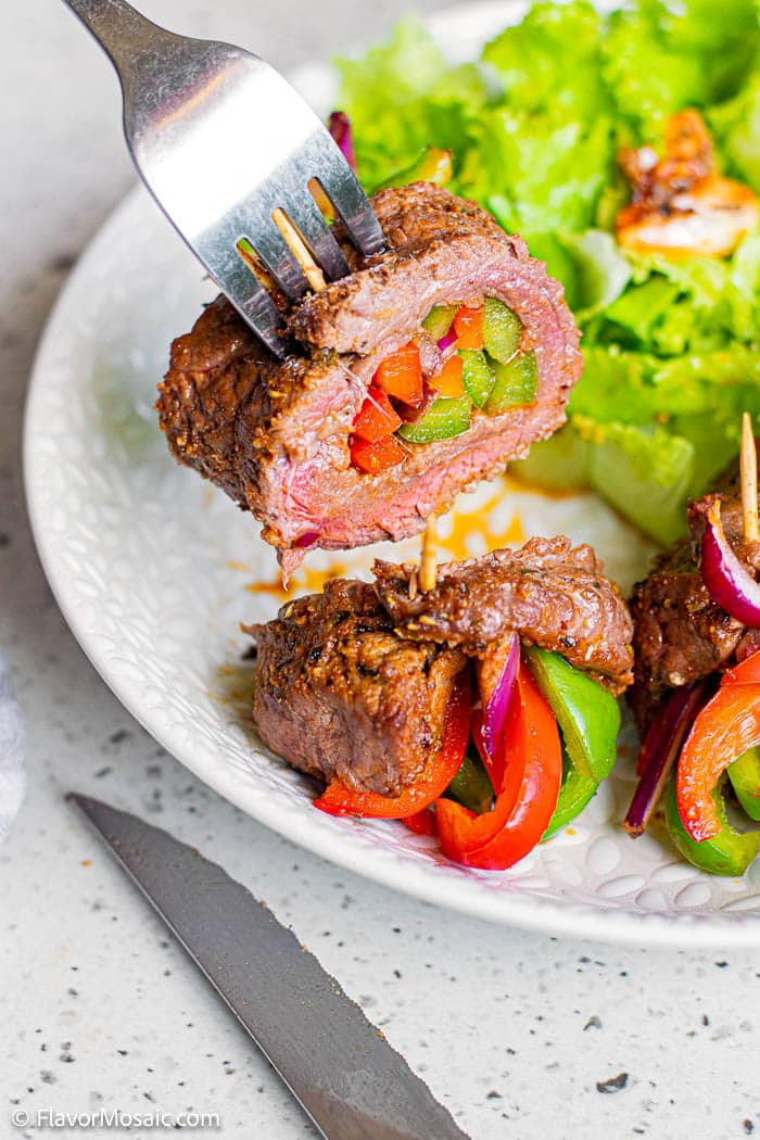 A metal dinner fork is lifting up a steak roll stuffed with red and green bell pepper over a white plate of more fajita met with red and green peppers and a green salad.