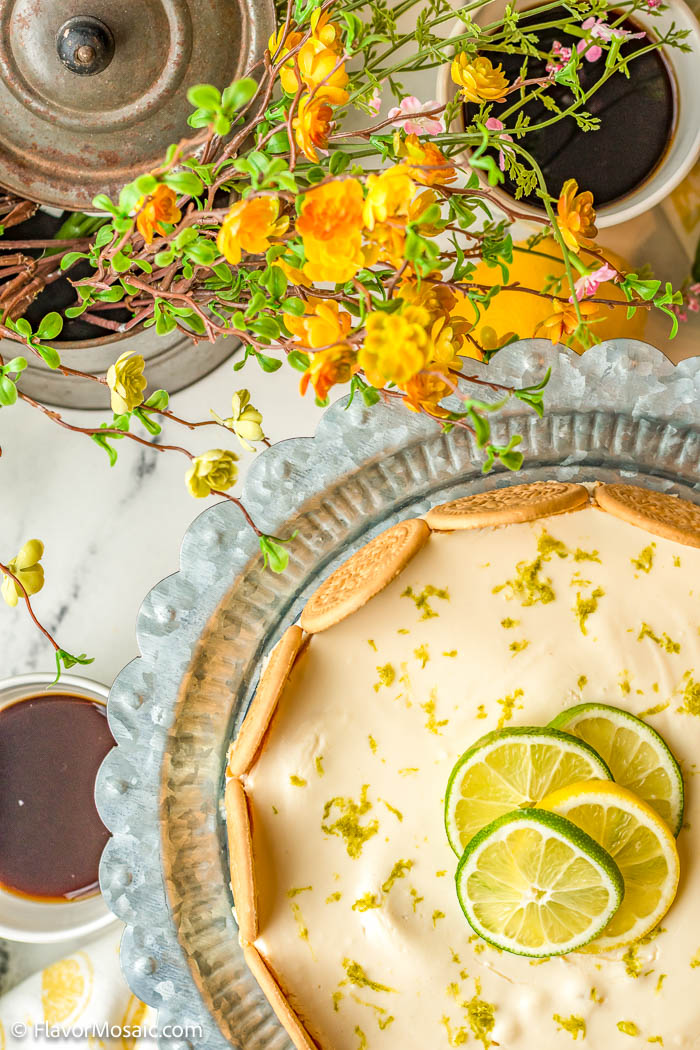 Overhead view partial whole lime charlotte cheesecake icebox cake in bottom right corner with yellow flowers and green leaves over cup of coffee and lid to bowl.