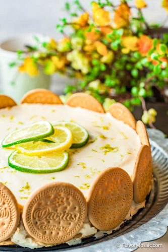 View of Lime Charlotte Ice Cream Cake Pie with yellow and orange flowers in the background.