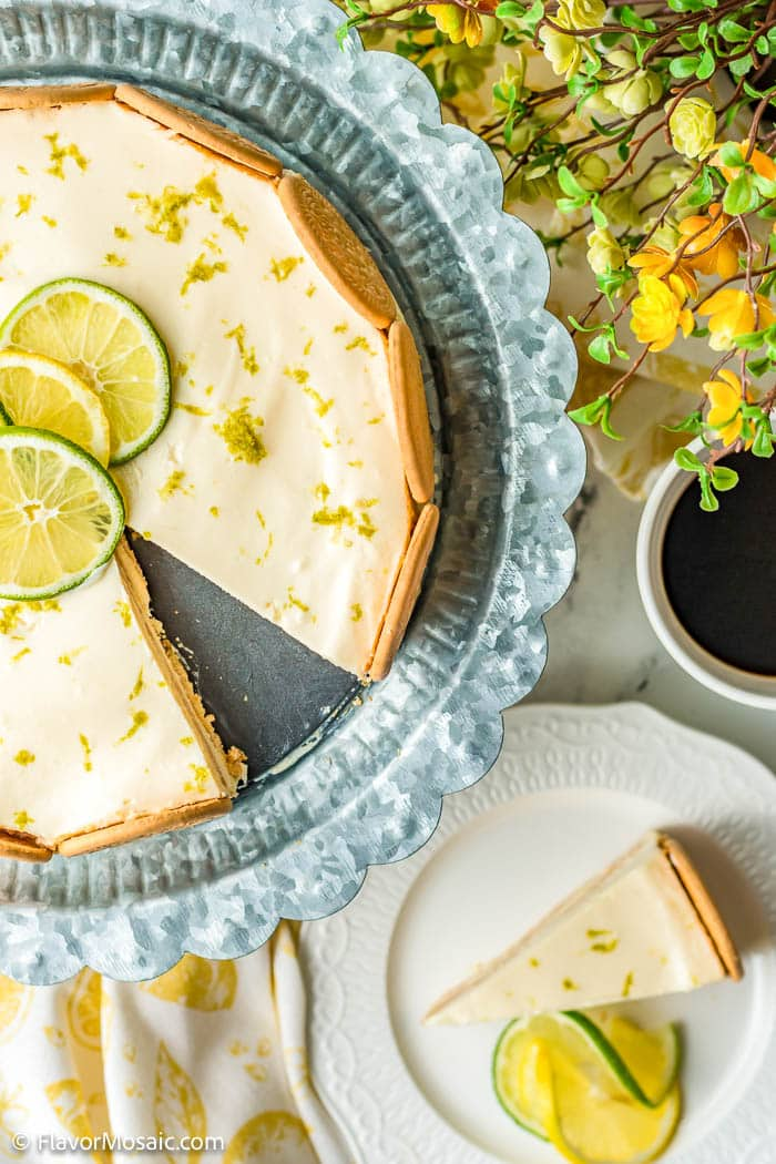 Overhead view of 2/3 pie in the upper left side of photo, with a slice of Lime Charlotte on a white serving plate with slices of lemon and lime with small yellow flowers with green leaves in the upper right corner and a white and soft yellow napkin in the bottom right corner.