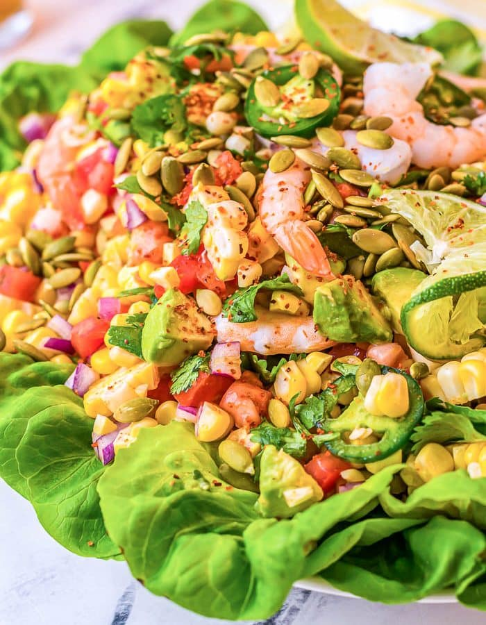 View of 2/3 of Mexican Shrimp Salad with green lettuce yellow corn pink shrimp, red peppers, and more!
