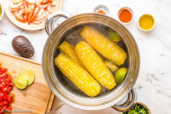 Overhead view of corn on the cob in a pot of water.