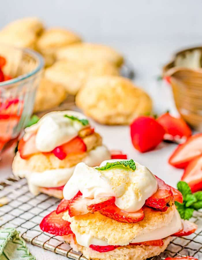 Side view of individual strawberry shortcakes on a wire baking rack with the focus on the front strawberry shortcake with others in the background on a blue gray counter.