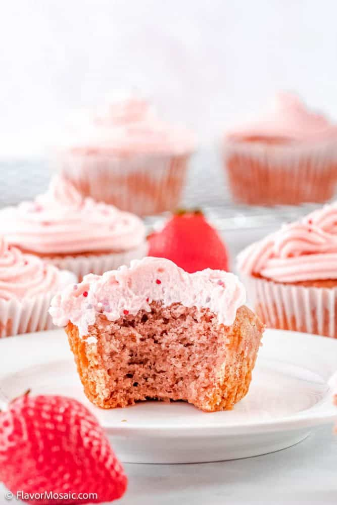 Side view of a white plate with a single cupcake with a large bite taken out of it so you can see the inside of the cupcake and the strawberry frosting. A whole strawberry sits in front of the plate in the bottom left corner and there are about 5 cupcakes in the background.