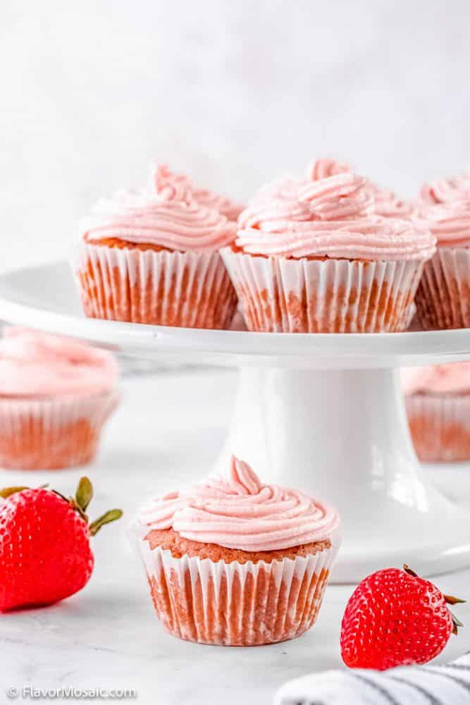 Side view of a cake stand with strawberry cupcakes with a cupcake under it surrounded by whole strawberries and more strawberry cupcakes in the background.