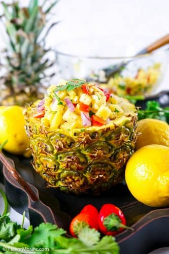 Side view of bottom half of pineapple, hollowed out and filled with pineapple salsa, surrounded by 3 whole lemons, 2 red chili peppers, cilantro, the top half of the pineapple in the back, along with a glass bowl of the remaining salsa.