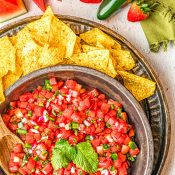 Overhead view of bowl with watermelon salsa surrounded by tortilla chips and slices of watermelon, whole jalapeños, strawberries, and a green napkin in the top right.