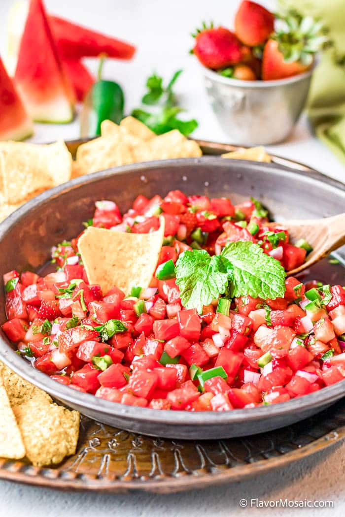 A large metal bowl of Watermelon Salsa with a tortilla chip and cilantro on top of a dark round pewter? plate with tortilla chips surrounding the bowl of salsa. Slices of Watermelon, a bowl of strawberries, a jalapeno, cilantro, and a green napkin are in the background.