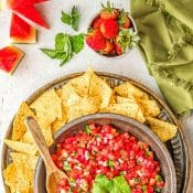 1-photo pin for Watermelon Salsa with overhead view of bowl of watermelon salsa on tray surrounded by tortilla chips. A green napkin, watermelon slices, and strawberries surround the tray.