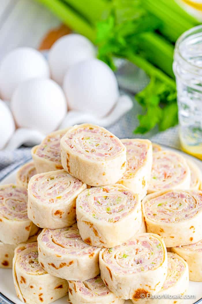 Photo of ham salad pinwheels sticked high on a plate with eggs and celery in the background.