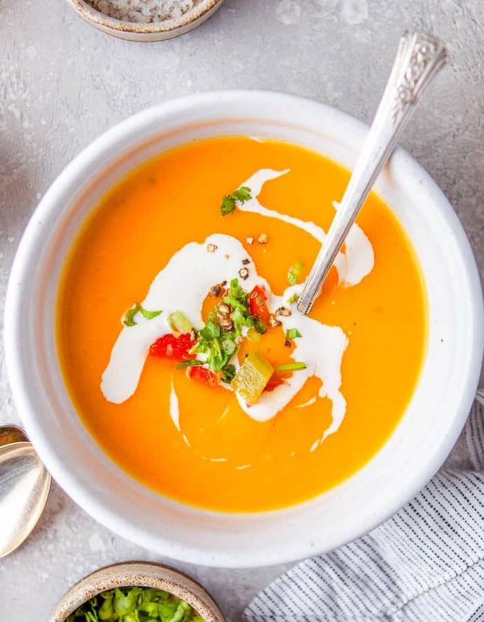 Overhead view of a small white bowl with a single serving of Instant Pot Butternut Squash Red Pepper Soup garnished with swirls of sour cream, chopped green onions, and chopped red bell peppers.