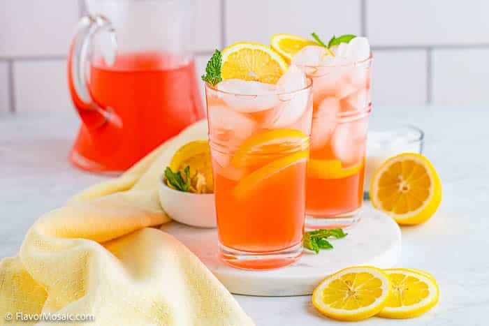 2 glasses of pink lemonade with ice cubes and sliced lemons and mint garnish sitting on white marble, surrounded by sliced lemons and lemon halves and mint leaves with a light yellow napkin next to it and a glass pitcher of lemonade in the back in front of a white tile backsplash.