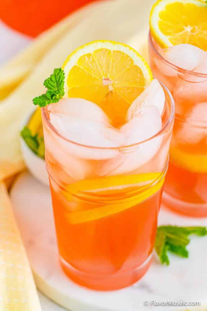 Glass of pink lemonade with ice and sliced lemons garnished with mint on white marble with yellow napkin. Partial view of a second glass of lemonade with a peek at the corner of the pitcher of lemonade in the back.