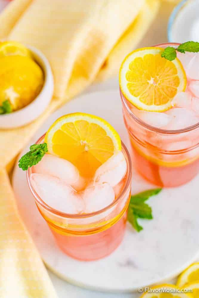 Looking down on 2 glasses of pink lemonade filled with ice, topped with slices of lemon and mint garnishes on white marble background with light yellow napkin on the left and a small bowl with more lemon slices.
