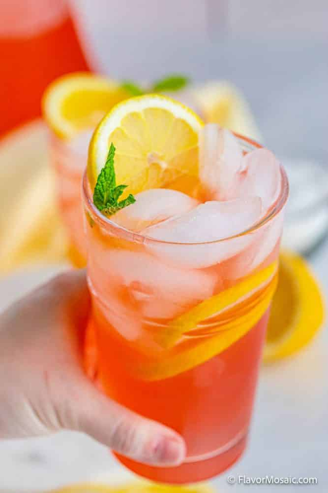 Someone's hand holding a glass of pink lemonade with ice cubes, sliced lemons, and a mint garnish.