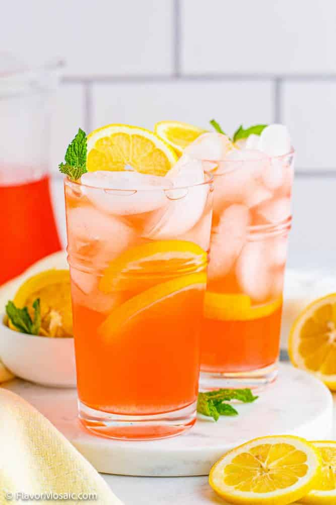 2 glasses of pink lemonade on a white counter with white tile backsplash with pitcher of pink lemonade in back and surrounded by lemon slices.