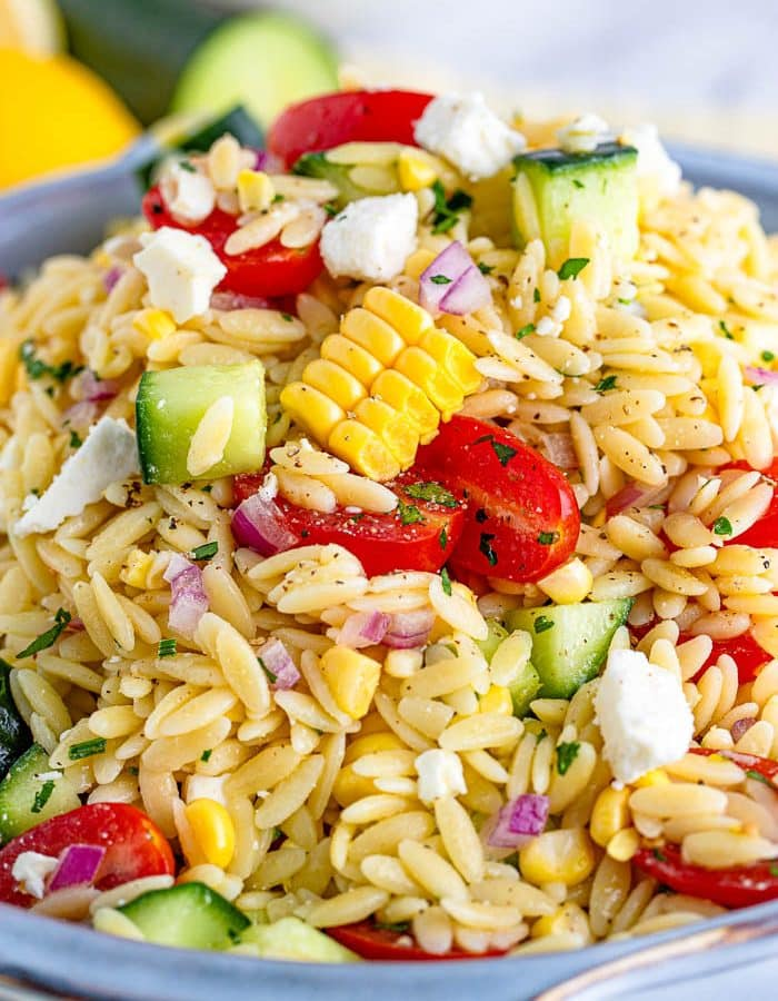 Close up of Orzo Pasta Salad with orzo, corn, peppers, and more in blue serving bowl.