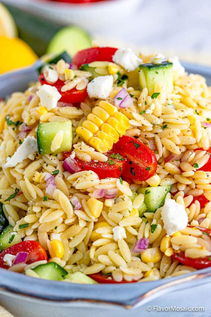 Close up of Orzo Pasta Salad with orzo, corn, peppers, cucumbers, tomatoes, and more in blue serving bowl.