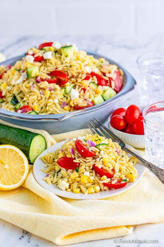 Large blue bowl of orzo pasta salad with tomatoes, corn, and more in the back with a small plate with serving of orzo pasta with fork in the front, surrounded by 1/2 lemon cucumber, small bowl of cherry tomatoes, and a glass of water.