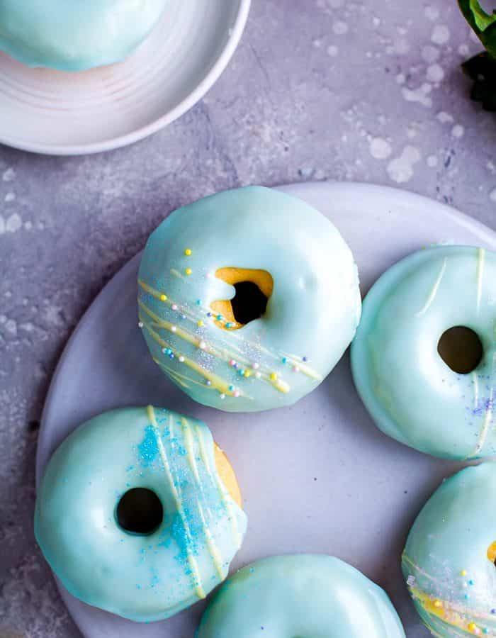Overhead view of a plate of donuts with a light blue glaze and yellow decorative frosting drizzled on top with small plate with single blue frosted donuts to the side in the upper left corner.