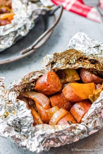 open foil dinner packet with sausage, potatoes, carrots, and onions.