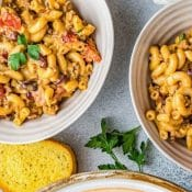 Single photo pin for Instant Pot Chili Mac with a red label with white text at the top and an overhead photo of a partial view of 3 bowls with Instant Pot Chili Mac with a piece of buttered toast and a sprig of cilantro in the middle.